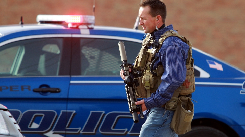 A Natrona County Sheriff's deputy in tactical gear leaves the scene of a reported homicide at Casper College in Casper, Wyoming on Friday, Nov. 30, 2012. (Casper Star-Tribune, Alan Rogers)