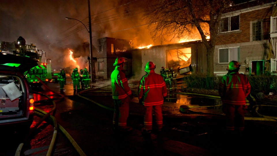 Firefighter battle a blaze in Montreal's East end on Friday Nov. 30, 2012. (Ryan Remiorz / THE CANADIAN PRESS)