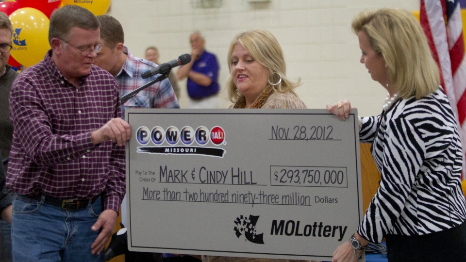 Mark, left, and Cindy, center, Hill are presented a check by a Missouri Lottery official during the announcement of Powerball winners in Dearborn, Mo., Friday, Nov. 30, 2012. (AP / Orlin Wagner)