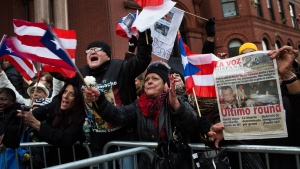 "Nelly Guzman, centre, of New York, waves a Puerto Rican flag as she waits to visit former boxing champion Hector ""Macho"" Camacho's casket at his wake in St. Cecilia's Roman Catholic Church in New York, Friday, Nov. 30, 2012. (AP / John Minchillo)"