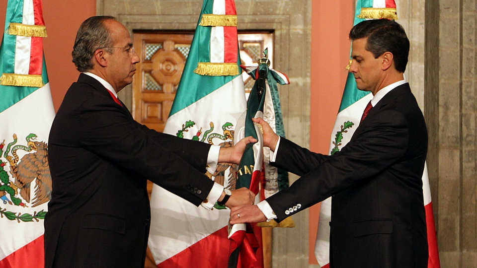 Mexico's outgoing president, Felipe Calderon, left, gives a Mexican flag to president-elect Enrique Pena Nieto during the official transfer of command ceremony at the National Palace in Mexico City, Saturday Dec. 1, 2012. (AP / Press Office of Enrique Pena Nieto)