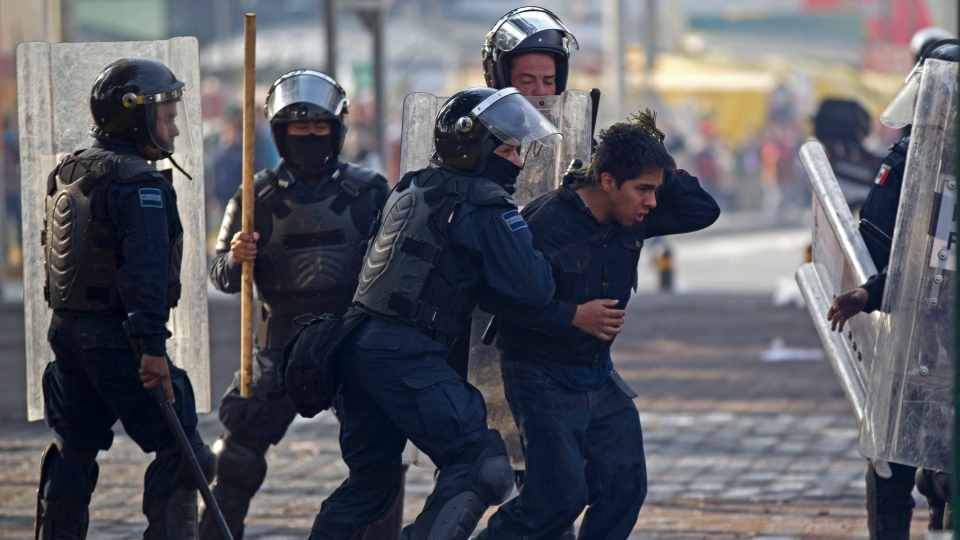 Riot police take away a protestor during clashes around the National Congress, where the swearing in of new Mexican President Enrique Pena Nieto is taking place in Mexico City, Saturday, Dec. 1, 2012. (AP / Eduardo Verdugo)