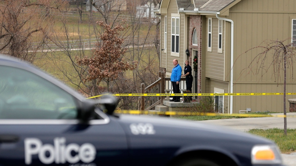 Investigators stand outside a house where police say Kansas City Chiefs linebacker Jovan Belcher fatally shot his girlfriend before driving to the NFL football team's training facility and shooting himself, in Independence, Mo., Saturday, Dec. 1, 2012. (AP / Charlie Riedel)