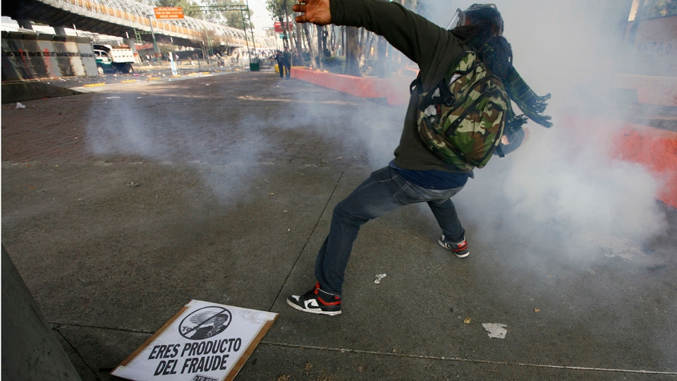 A demonstrator throws a stone to police during protests against new Mexican President Enrique Pena Nieto's rule, outside the National Congress, in Mexico City, Saturday, Dec. 1, 2012. (AP / Marco Ugarte)