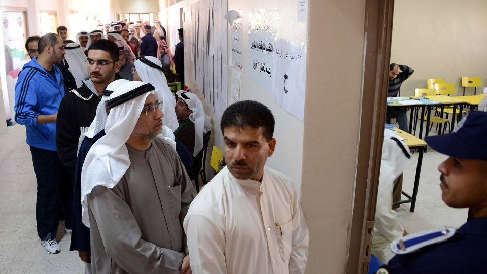 Kuwaiti citizens wait in line to cast their vote at a polling station in Rumaithiya, Kuwait on Saturday, Dec. 1, 2012. (AP / Gustavo Ferrari)