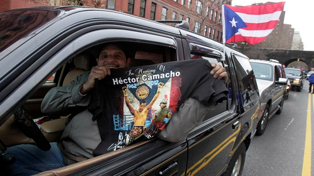 A man in the funeral procession of boxer Hector 'Macho' Camacho shows a commemorative tee- shirt after services at St. Cecilia's Roman Catholic Church in New York, Dec. 1, 2012. Doctors pronounced Camacho dead on Nov. 24, after he was removed from life support at his family's direction. He never regained consciousness after at least one gunman crept up to his car in a darkened parking lot in Puerto Rico and opened fire. (AP / Richard Drew)
