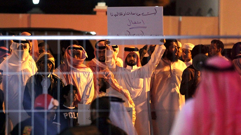Bahraini protesters chant slogans and one holds a banner that reads,