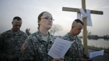 U.S. soldiers read verses as they celebrate Easter with a sunrise service at Camp Victory, in Baghdad, Iraq, Sunday, March 23, 2008. (AP Photo/Dusan Vranic)