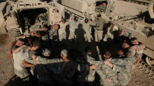 U.S. Army troops from Alpha Company,1st Battalion, 5th Cavalry Regiment, 2nd Brigade, 1st Cavalry Division pray in a circle prior to an operation in the Amariyah neighborhood of west Baghdad, Iraq on Tuesday Aug. 14, 2007. (AP Photo/Petr David Josek)