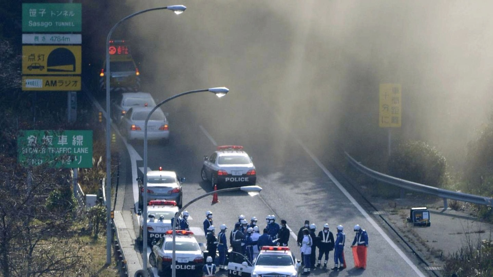Police vehicles are parked at the entrance as smoke billows out of the Sasago Tunnel on the Chuo Expressway in Koshu, Yamanashi Prefecture, central Japan, Sunday morning, Dec. 2, 2012. (AP / Kyodo News)