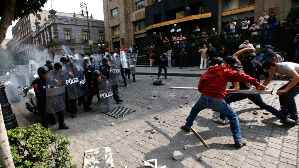 Protestors attempt to intimidate riot police with a pole in the streets of downtown Mexico City, Saturday, Dec. 1, 2012. (AP / Marco Ugarte)