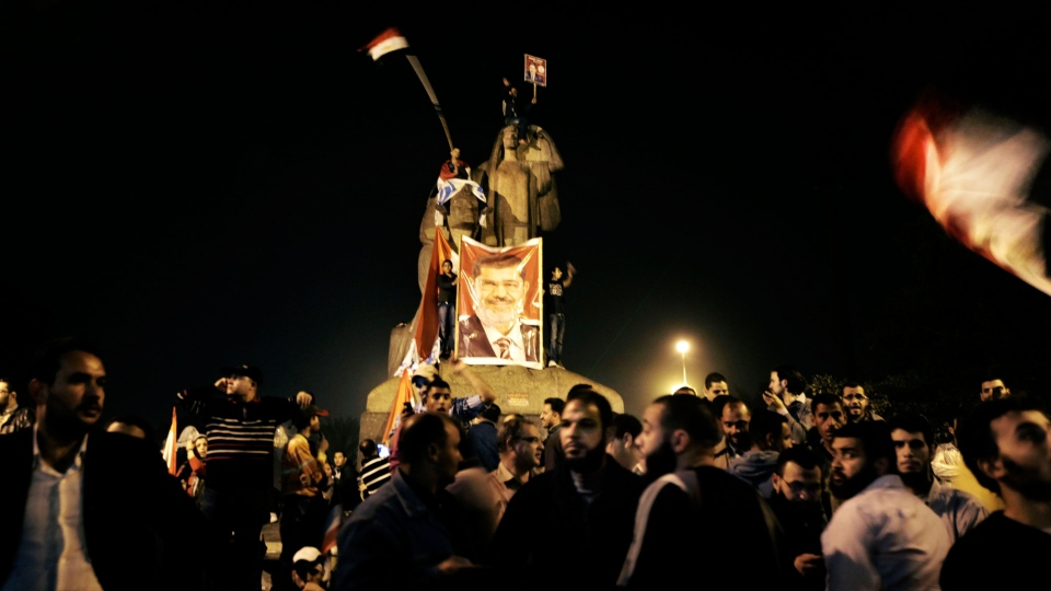 People wave Egyptian flags and hold a large poster with the portrait of President Mohammed Morsi, center, during a rally near Cairo University in Cairo, Egypt, Saturday, Dec. 1, 2012. (AP / Nariman El-Mofty)