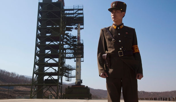 A North Korean soldier stands in front of the country's Unha-3 rocket, slated for liftoff between April 12-16, at Sohae Satellite Station in Tongchang-ri, North Korea, April 8, 2012. (AP / David Guttenfelder)