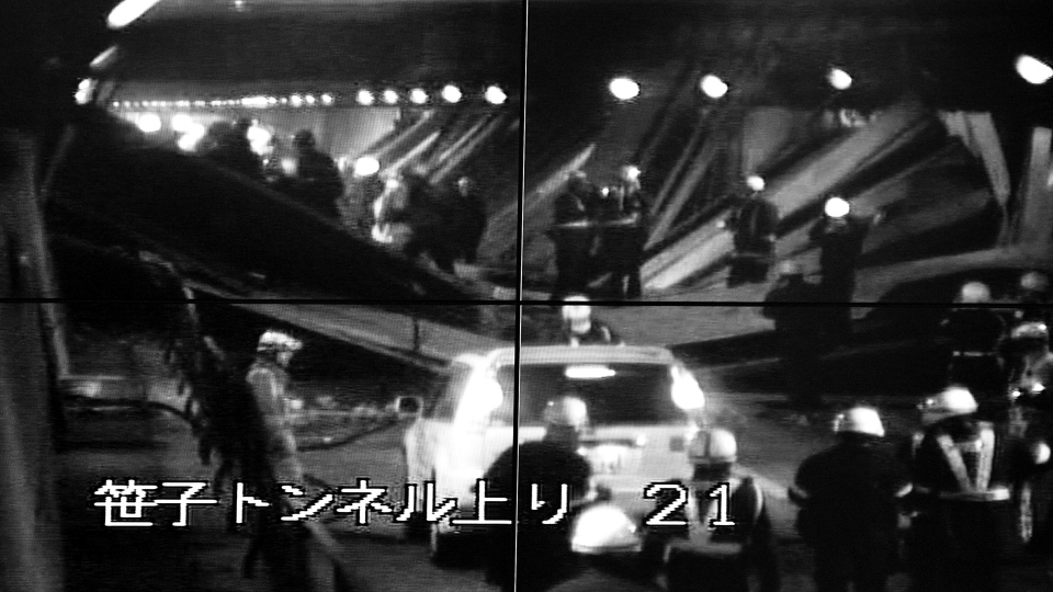 This image taken from the monitoring camera of Central Nippon Expressway's Hachioji branch, Tokyo, shows the rescuers looking for the injured among fallen roof panels in the Sasago Tunnel, Yamanashi Prefecture, central Japan, Sunday, Dec. 2, 2012. (To Tokyo)