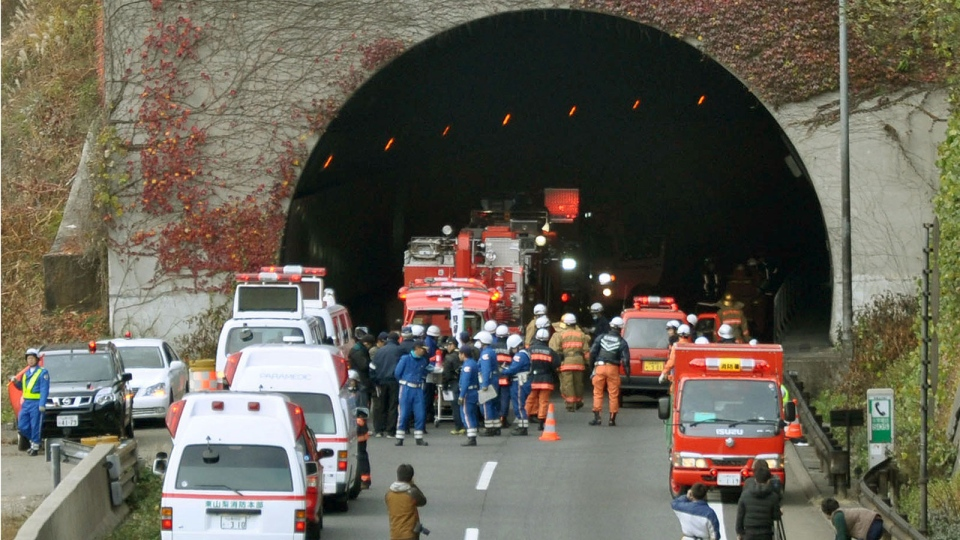 Police officers and firefighters gather at the exit of the Sasago Tunnel on the Chuo Expressway in Otsuki, Yamanashi Prefecture, central Japan, Sunday morning, Dec. 2, 2012. (AP / Kyodo News)