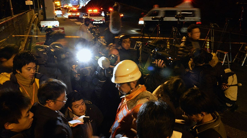 A worker of Central Nippon Expressway Co. speaks to the reporters near the Sasago Tunnel where a collapse took place in Koshu, Yamanashi Prefecture, central Japan, Sunday, Dec. 2, 2012. (AP / Kyodo News)