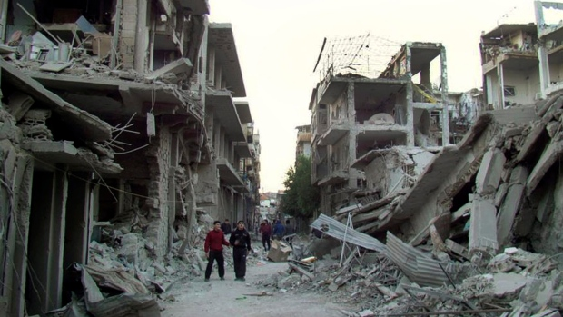 Syrian citizens walk in a destroyed street