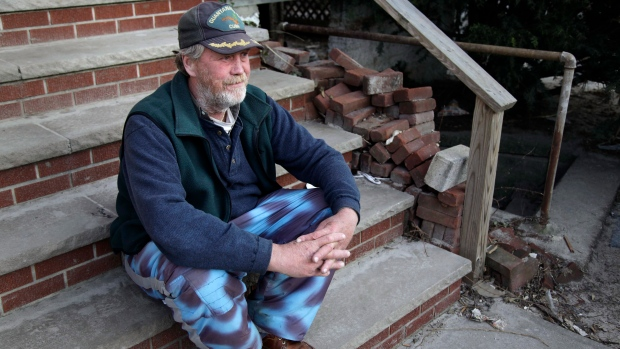John Frawley sits on the porch of his house