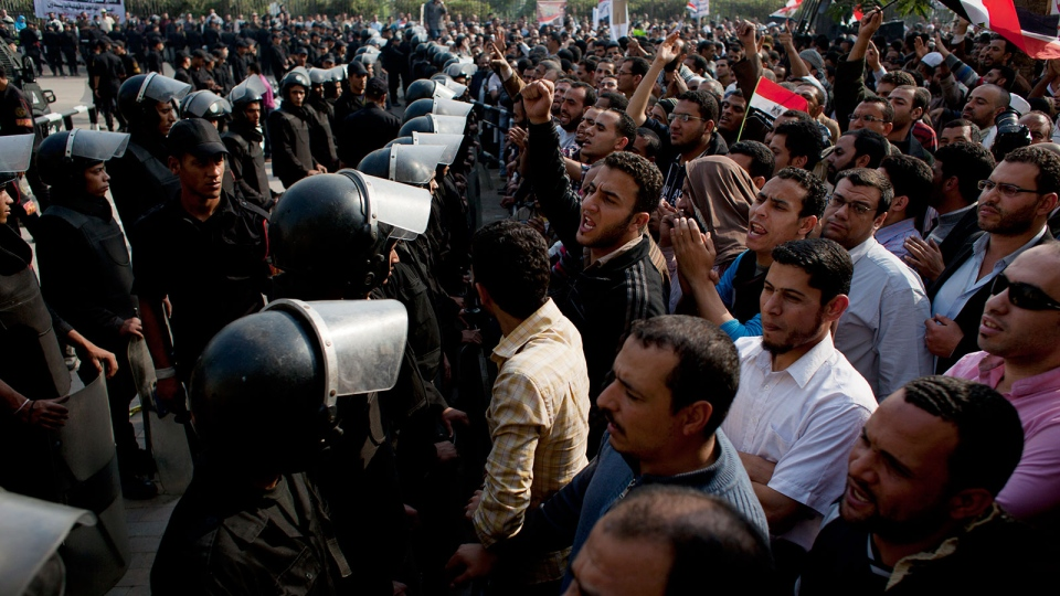 Supporters of Egyptian President Mohammed Morsi chant slogans as riot police stand guard in front of the entrance of Egypt's top court, in Cairo, Egypt, Sunday, Dec. 2, 2012. (AP / Nasser Nasser)