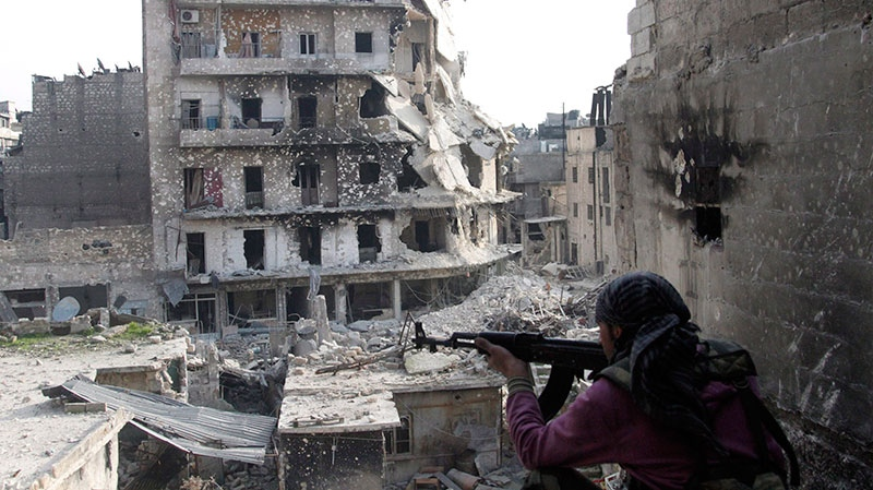 A Free Syrian Army fighter is in position in front of destroyed buildings in Aleppo, Syria, Thursday, Nov. 29, 2012. (AP)