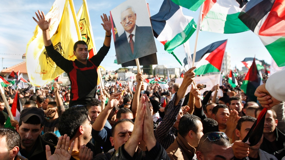 Palestinians wave flags and pictures of Palestinian President Mahmoud Abbas as they celebrate their successful bid to win UN statehood recognition in the West Bank city of Ramallah, Sunday, Dec. 2, 2012. (AP / Majdi Mohammed)