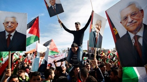 Palestinians hold pictures of Palestinian President Mahmoud Abbas, as they celebrate their successful bid to win U.N. statehood recognition in the West Bank city of Ramallah, Sunday, Dec. 2, 2012. (AP / Majdi Mohammed)