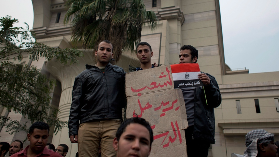 "Supporters of Egyptian President Mohammed Morsi hold a placard with Arabic that reads, ""the people want to solve the constitution,"" outside Egypt's top court in Cairo, Sunday, Dec. 2, 2012. (AP / Nasser Nasser)"