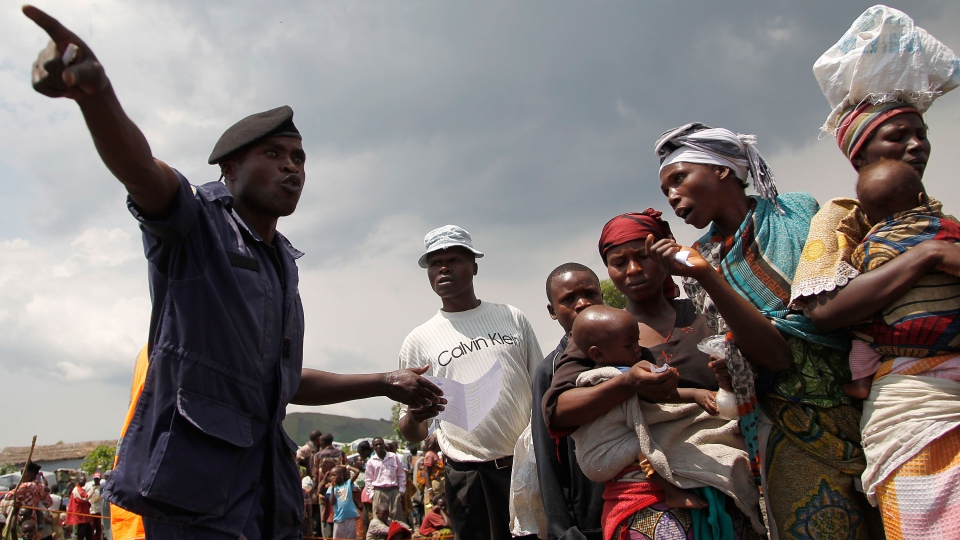 A Congolese national police officer directs internally displaced Congolese women waiting for food to be distributed by WFP at the Mugunga 3 camp outside the eastern Congolese town of Goma Sunday Dec. 2, 2012. (AP / Jerome Delay)