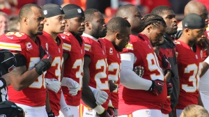 Kansas City Chiefs players stand arm-in-arm during a moment of silence before an NFL football game against the Carolina Panthers at Arrowhead Stadium in Kansas City, Mo., Sunday, Dec. 2, 2012. (AP / Colin E. Braley)