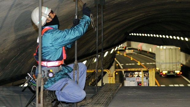 A worker inspects the interior of the 1.65-kilometre Tsuburano Tunnel on the Tomei Expressway in Yamakitamachi, Japan on Monday, Dec. 3, 2012. (AP Photo/Kyodo News)