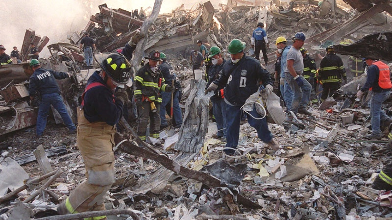 In this Sept. 13, 2001 file photo, firefighters and emergency personnel remove debris from the site of the World Trade Center towers' collapse in New York. (AP / Stephen Chernin)