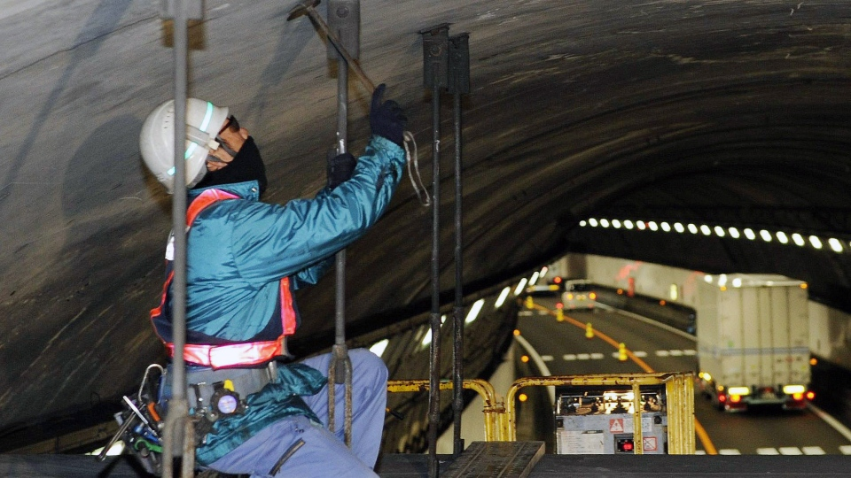 A worker inspects the structure inside the 1.65 kilometre Tsuburano Tunnel on the Tomei Expressway in Yamakitamachi, Kanagawa Prefecture, eastern Japan, Monday, Dec. 3, 2012. (AP / Kyodo News)