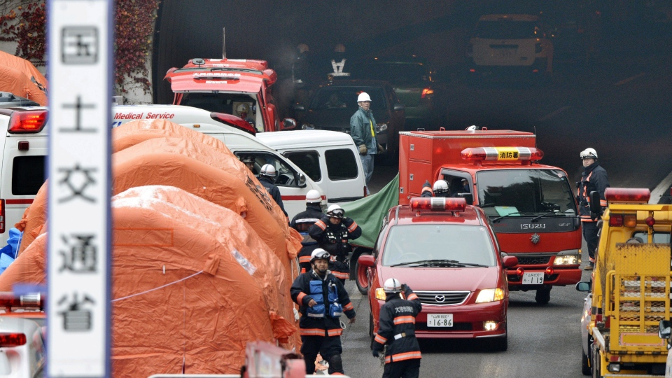 Firefighters work at the exit of the Sasago Tunnel on the Chuo Expressway in Otsuki, Yamanashi Prefecture, central Japan, Monday, Dec. 3, 2012. (AP / Kyodo News)