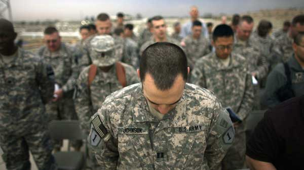 U.S. army soldiers bow their heads in prayer during Easter sunrise service in Camp Liberty, Baghdad, Iraq, Sunday, April 12, 2009. (AP Photo/Marko Drobnjakovic)