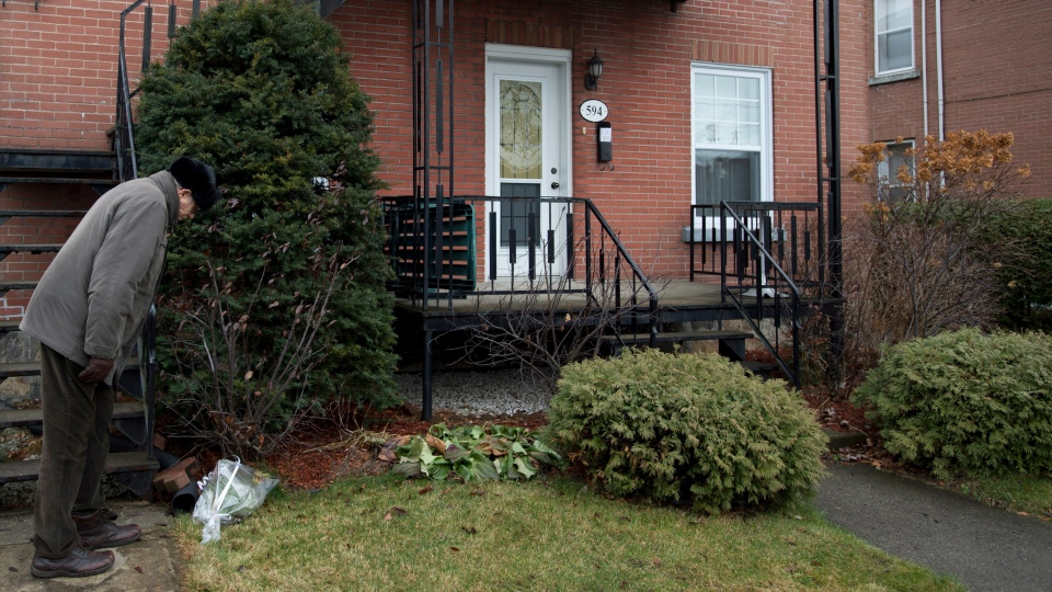 A local resident looks at flowers placed in front of a house, where three young siblings were found dead in the family dwelling in Drummondville, Que., on Monday, Dec. 3, 2012.  (Paul Chiasson / THE CANADIAN PRESS)