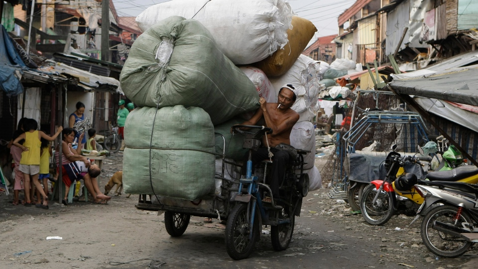 A Filipino man negotiates his motorized bicycle along a dirt road as he brings loads of used plastics which he will sell at a junk shop in a poor district in Manila, Philippines, on Monday Dec. 3, 2012. (AP / Aaron Favila)