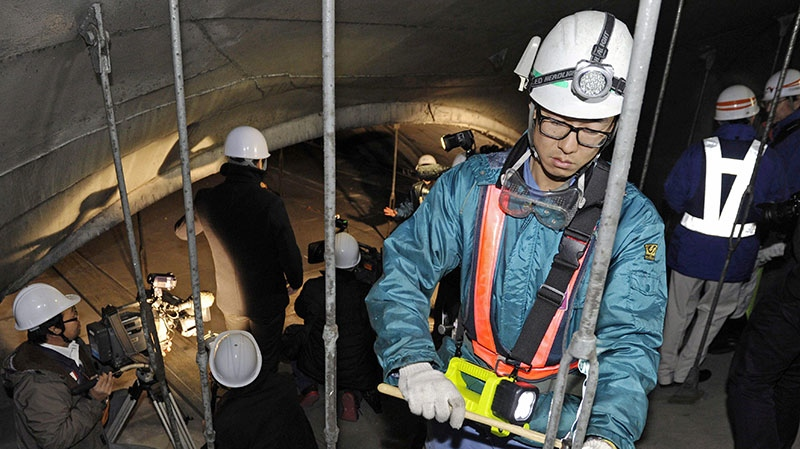 Workers inspect the structure inside the 1.65-kilometer (1-mile) Tsuburano Tunnel on the Tomei Expressway in Yamakitamachi, Kanagawa Prefecture, eastern Japan, Monday, Dec. 3, 2012. (AP / Kyodo News)