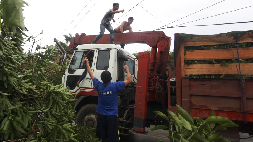 Workers clear a highway of toppled trees after Typhoon Bopha made a landfall in Compostela Valley in southeastern Philippines Tuesday Dec. 4, 2012. (AP / Karlos Manlupig)