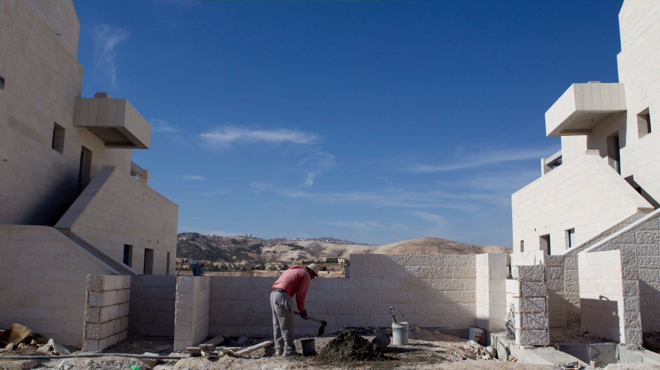 A Palestinian man works at a new housing development in the Jewish West Bank settlement of Maaleh Adumim, near Jerusalem, Sunday, Dec. 2, 2012. (Ariel Schalit/AP)