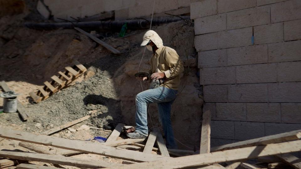 A Palestinian man works at a new housing development in the Jewish West Bank settlement of Maaleh Adumim, near Jerusalem, Sunday, Dec. 2, 2012. (AP / Ariel Schalit)