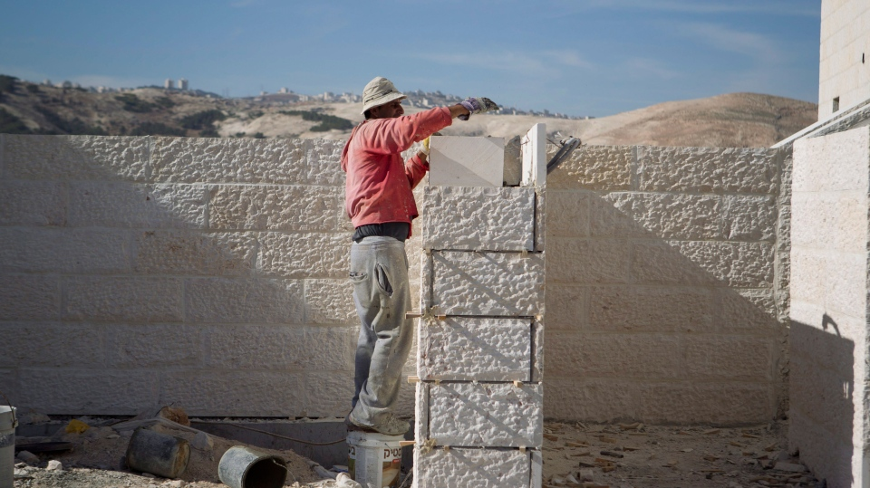 A Palestinian man works at a new housing development in the Jewish West Bank settlement of Maaleh Adumim, near Jerusalem, Sunday, Dec. 2, 2012. (AP / Ariel Schalit)