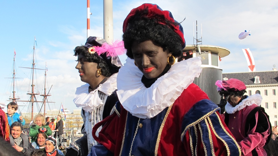 "Persons dressed as ""Zwarte Piet"" or ""Black Pete"" attend a parade after St. Nicholas, or Sinterklaas, arrived by boat in Amsterdam, Netherlands, Nov. 18, 2012. (AP / Margriet Faber)"