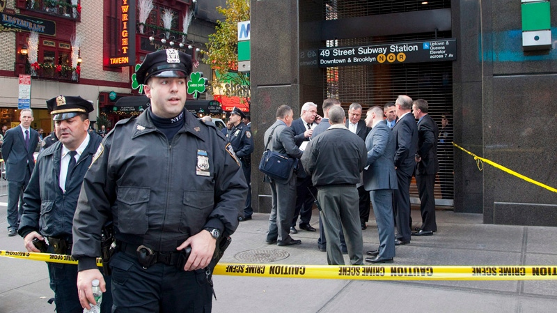 Uniformed and plainclothes police officers stand outside a New York subway station after a man was killed after falling into the path of a train, Monday, Dec. 3, 2012. (AP / Mark Lennihan)