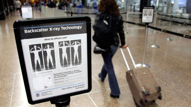 In this Nov. 19, 2010 file photo, a passenger walks past a sign informing travelers about the use of full-body scanners for TSA security screening at Seattle-Tacoma International Airport in Seattle. (AP / Ted S. Warren)
