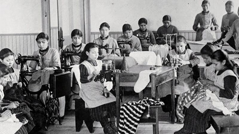 This file photo shows students at a residential school being taught how to sew.