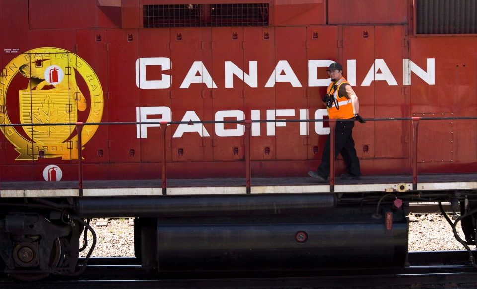 A Canadian Pacific Railway employee walks along the side of a locomotive in a marshalling yard in Calgary, Wednesday, May 16, 2012. (Jeff McIntosh / THE CANADIAN PRESS)