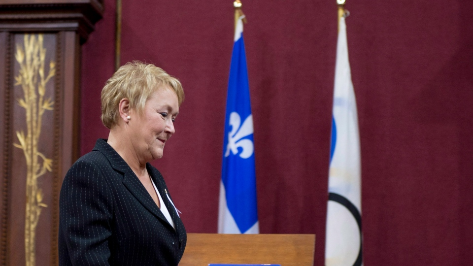 Quebec Premier Pauline Marois walks in front of the Quebec and Olympic flags at the legislative council room Tuesday, December 4, 2012 at the legislature in Quebec City. (Jacques Boissinot / THE CANADIAN PRESS)