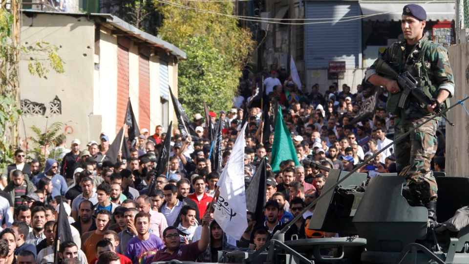 An army soldier stands guard as supporters of Lebanese anti-Syrian regime and Salafist group leader Sheikh Ahmad al-Assir attend a protest against the Syrian regime in southern port city of Sidon, Lebanon, Sunday, Dec. 2, 2012. (AP / Mohammed Zaatari)