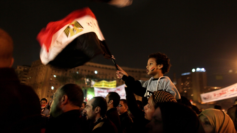 A young Egyptian boy waves a national flag from his mother's shoulders as protesters chant slogans in Tahrir Square in Cairo, Egypt, Tuesday, Dec. 4, 2012. (AP / Maya Alleruzzo)