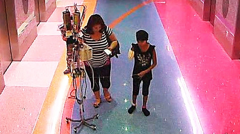 A woman is seen with her 11-year-old daughter, a leukemia patient who had her arm amputated and a heart catheter inserted due to an infection on Monday, Dec. 3, 2012. (Phoenix Police Department)